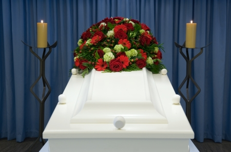 trumna: A white coffin in a mortuary with a flower arrangement
