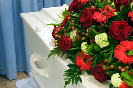 coffins: A white coffin in a mortuary with a flower arrangement