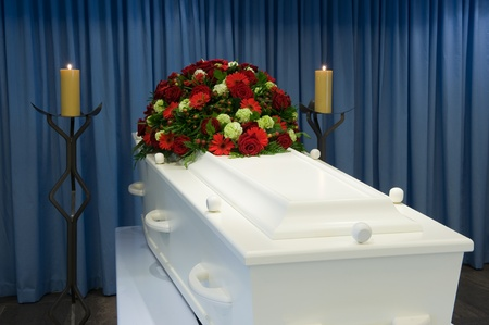 A white coffin in a mortuary with a flower arrangement photo