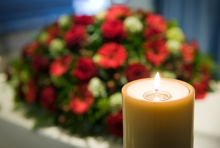 Eine brennende Kerze mit einem weiß Sarg und ein Blumenarrangement im Hintergrund in einer Leichenhalle