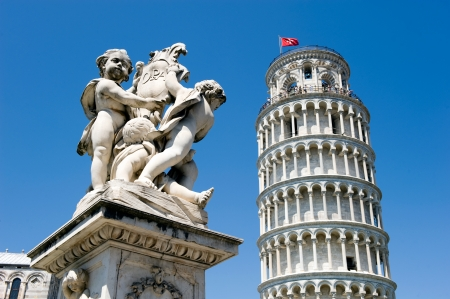 The hanging tower of Pisa with statue in front photo