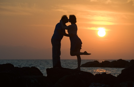A couple by sunset on a pier kissing each other photo