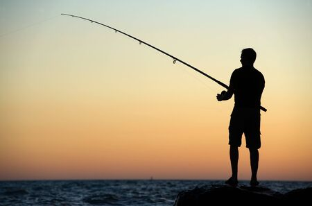 handline fishing: MARINA DE LA MAR, ITALY -AUGUST 08:  A man is fishing in his vacation on a pier during sunset. On a beautiful evening in August on the mediterranean coast, August 08, 2011 in Marina De La Mar in Italy.