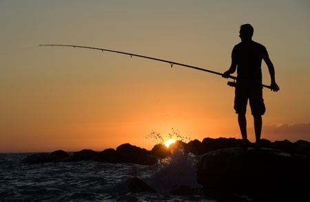 MARINA DE LA MAR, ITALY -AUGUST 08:  A man is fishing in his vacation on a pier during sunset. On a beautiful evening in August on the coast of the  mediterranean sea, August 08, 2011 in Marina De La Mar in Italy.