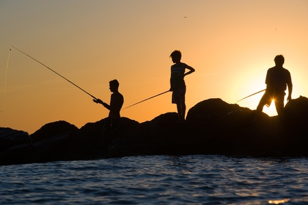 handline fishing: MARINA DE LA MAR, ITALY -AUGUST 08:  Three people are fishing in their vacation on a pier during sunset. On a beautiful evening in August on the coast of the mediterranean sea, August 08, 2011 in Marina De La Mar in Italy.