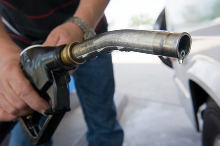 petrol pump: A drop of diesel fuel hanging on a fuel nozzle