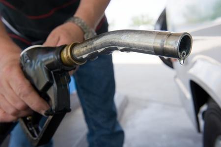 bomba de gasolina: Una gota de combustible diesel que cuelgan en una boquilla de combustible