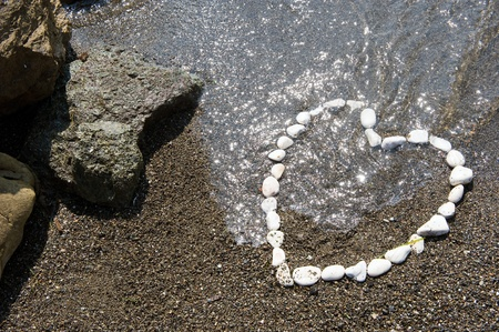 heart in sand: A heart made with white stones on a beach Stock Photo