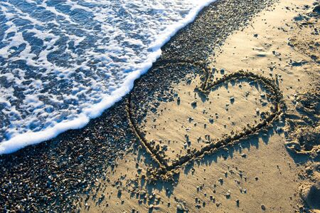 A heart drawn in sand on a beach