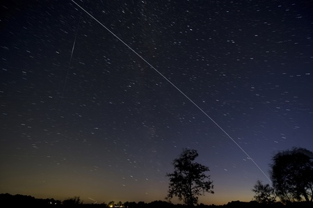 The ISS crossing by over the eveningsky just after dawn in the Netherlands. Left a reflection of the sun on a passing satellite. 4 minutes exposure. Editorial