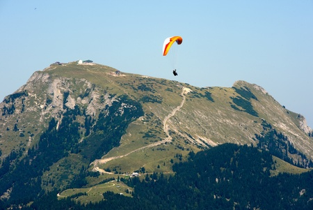 gliding: A paraglider is gliding in front of the Schafberg in Austria.