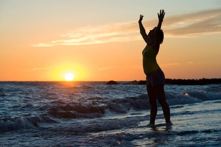 A happy woman enjoying the sunset on the beach. photo