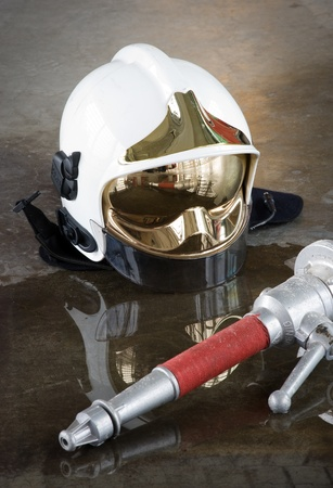 A helmet and a nozzle on the floor in a firestation used by firefighters