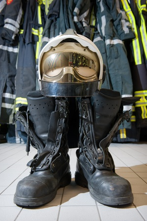 fire fighting equipment: A helmet and bootz on the floor in a firestation ready to be used by firefighters