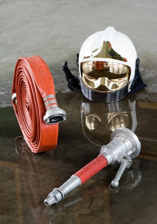 A helmet, a firehose and a nozzle on the floor in a firestation used by firefighters