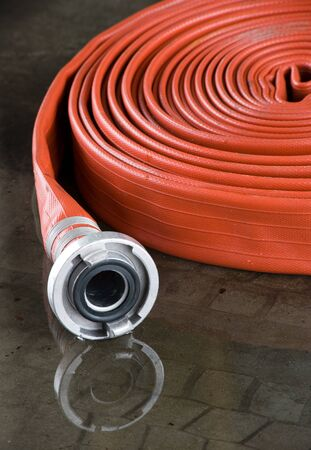 A rolled up firehose on the floor in a firestation used by firefighters