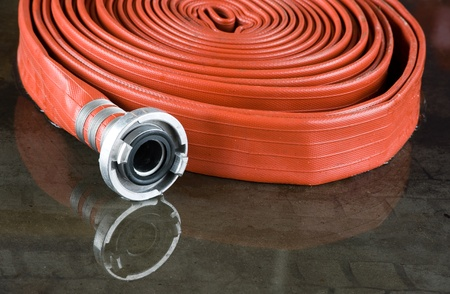 A rolled up firehose on the wet floor in a firestation used by firefighters Editorial