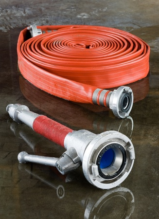 A rolled up firehose and a nozzle on the wet floor in a firestation used by firefighters Editorial