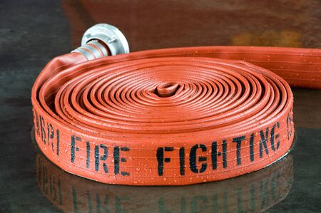 A rolled up firehose on the wet floor in a firestation used by firefighters