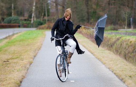 A young woman is fighting against the storm on het bicycle Stock Photo - 11437634