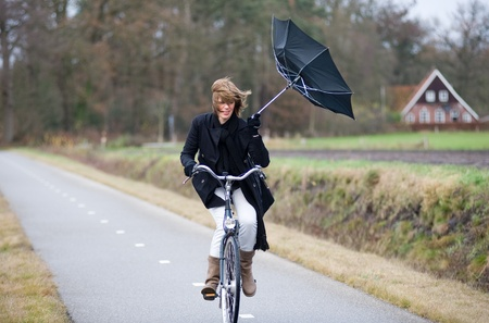 typhoon: A young woman is fighting against the storm on her bicycle