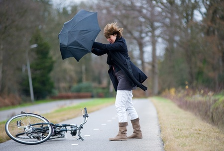 windstorm: A young woman is fighting against the storm after she has fallen with her bicycle.