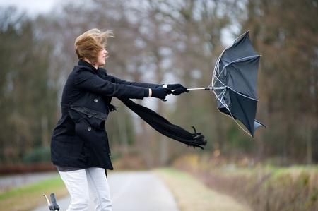 若い女性は彼女の傘で嵐を戦っています。