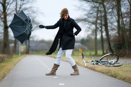 A young woman is fighting against the storm with her umbrella photo