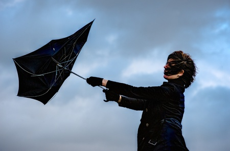 windstorm: A young woman is fighting against the storm with her umbrella