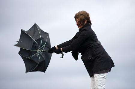 若い女性は、彼女の傘の嵐と戦っています。