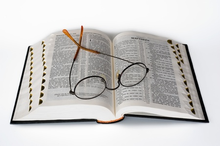 An open bible with a glasses lying on it photo