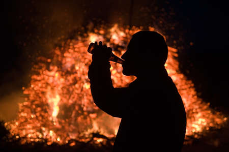 outdoor fireplace: A man drinking beer in front of a huge bonfire, a tradition with easter in North-West Europe