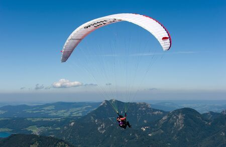 skydive: St GILGEN, AUSTRIA - AUGUST 18  A paraglider is flying of the mountain down to the city of St Gilgen on the banks of the Wolfgangsee  The zwolferhornmountain is popular by paragliders because of it