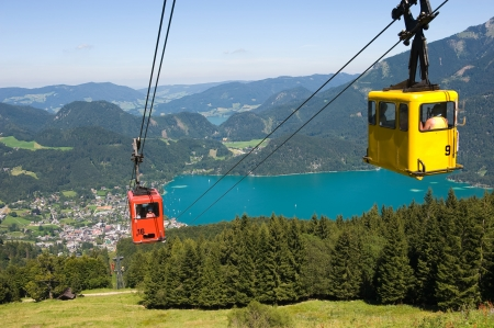 A cableway is bringing tourists up the zwolferhornmountain near the city of st Gilgen in Austria