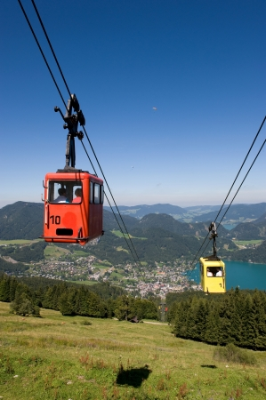 cableway: A cableway is bringing tourists up the zwolferhornmountain near the city of st Gilgen in Austria