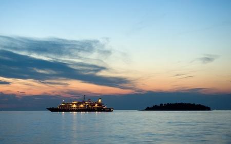 luxury liner: A cruise ship in the twilight in the adriatic sea for the coast of Croatia Stock Photo