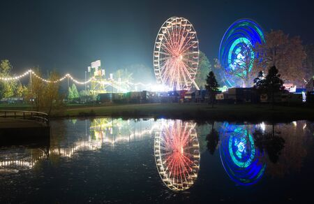 The lights of two ferris wheels and an amusement park reflected in the water of a pond Stock Photo - 15950929