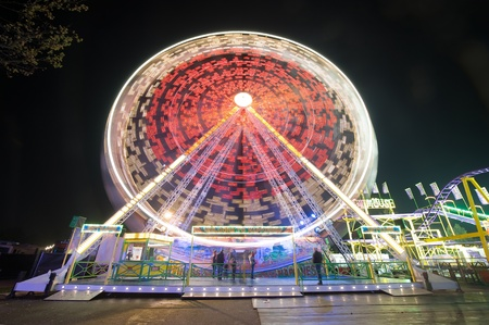 A turning ferris wheel in the evening at an amusement park