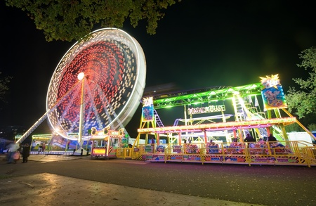 A ferris wheel and a little rollercoaster in the evening at an amusement park Stock Photo - 15950708