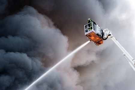 A fire fighter at work in a hydraulic hoist Stock Photo