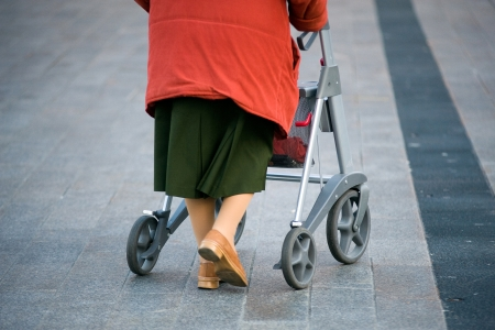 An elderly woman walking on the street with her walking frame photo