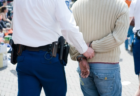 being arrested: A criminal is being arrested with handcuffs on his back