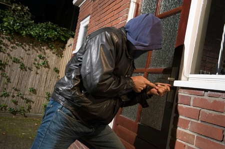 A burglar trying to get into a house by the backdoor photo