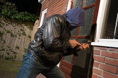 Un ladrón tratando de entrar en una casa por la puerta trasera Foto de archivo