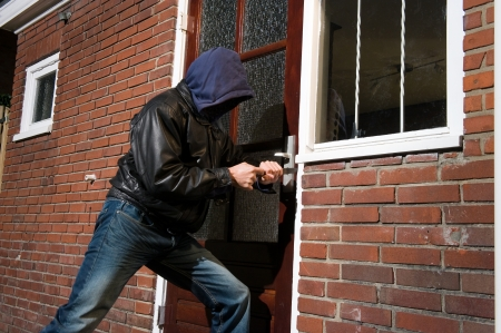 A Burglar Trying To Get Into A House By The Backdoor Stock Photo   16616874