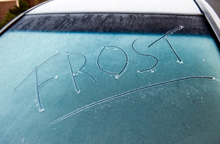 The word frost written on a frozen car screen photo