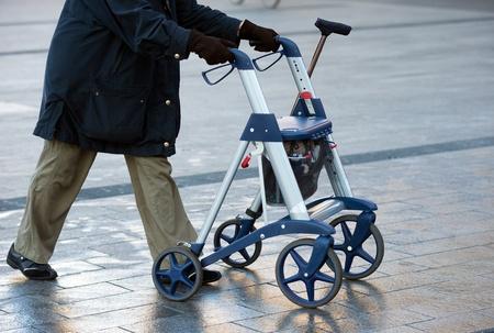 高齢者の女性彼女の歩行のフレームと通りを歩いて