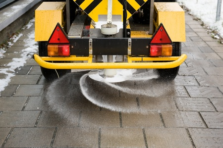 snow clearing: A machine is sprinkling salt on a sidewalk Stock Photo