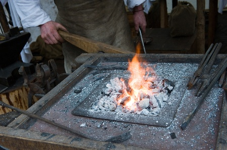 smithery: Blacksmith pumping up oxygen through the fire to heat it up Stock Photo