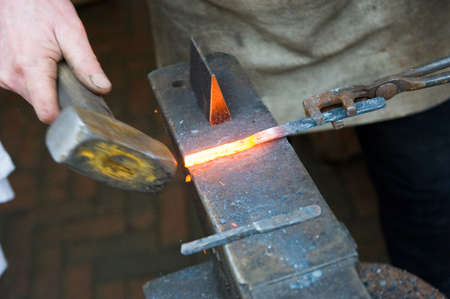 forgeman: Blacksmith at work with a hammer an glowing hot iron